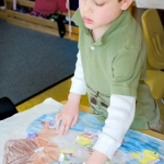 A Children's House student painting a  detailed map of Europe in his classroom.