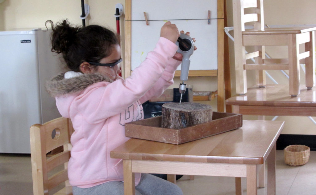 Child using hand crank drill