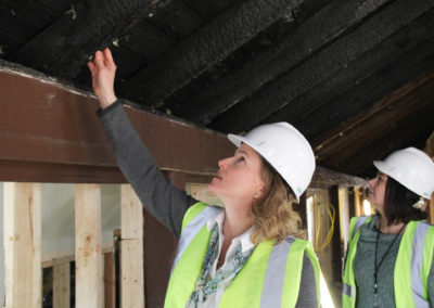 Head of School, Tamara Balis, evaluating the fire damage to the rafters